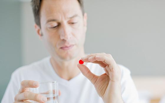 Мужчина принимает лекарство