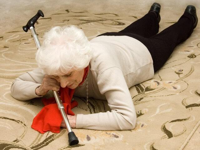 Пожилая женщина лежит на полу