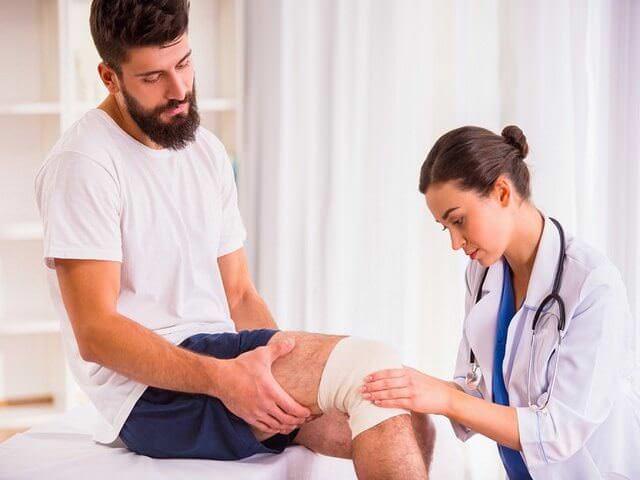 Доктор осматривает ногу мужчине